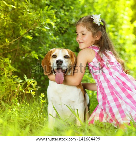 Cute little girl is playing with her dog in the green park