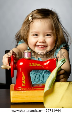 Cute little girl is playing with sewing machine