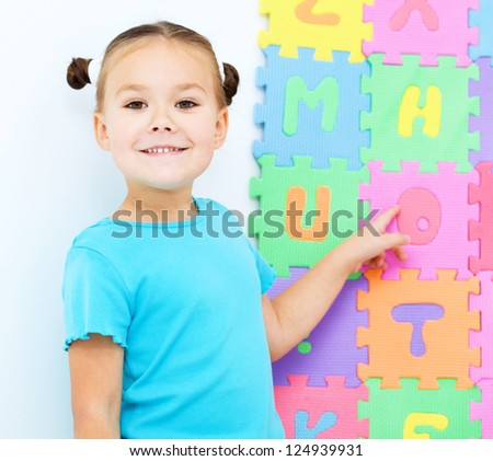 Cute little girl is pointing at letter O on alphabet - stock photo
