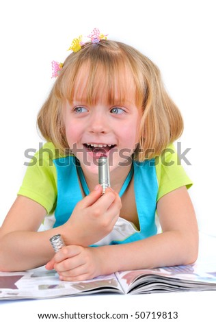 Cute little girl is putting on a make up - stock photo