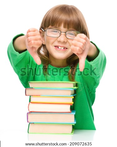 Cute little girl is reading a book and showing thumb down sign using both hands, isolated over white - stock photo