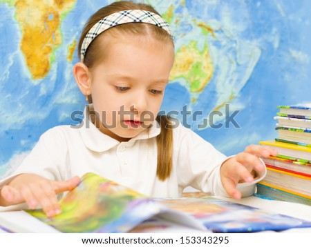 Cute little girl is reading a book in front of world map in preschool - stock photo
