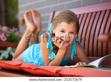 Cute little girl is reading a book while laying on bench - stock photo