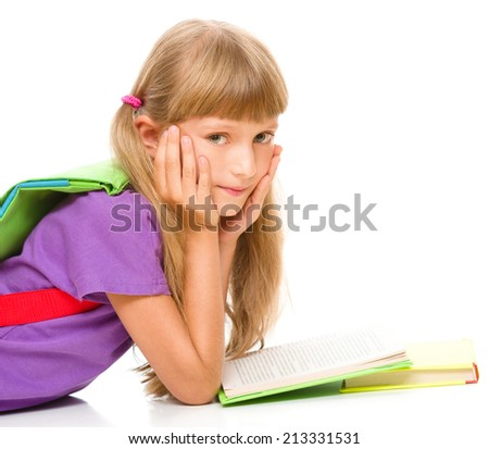 Cute little girl is reading a book while laying on floor, isolated over white - stock photo
