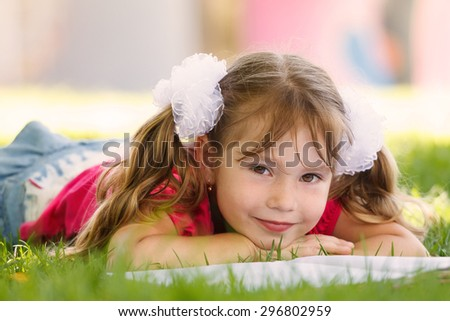 Cute little girl is reading a book while lying on green grass looking to the camera - stock photo
