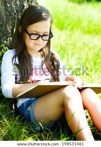 Cute little girl is reading a book while sitting on green grass - stock photo