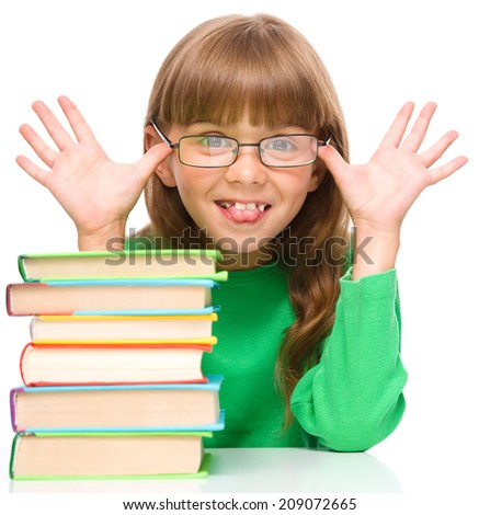Cute little girl is reading a book while wearing glasses and showing funny grimace, isolated over white - stock photo