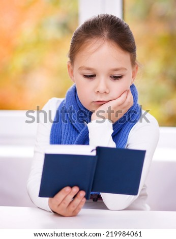 Cute little girl is reading book while sitting at table, indoor shoot - stock photo