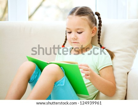 Cute little girl is reading book while sitting on a couch, indoor shoot - stock photo