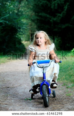 Cute little girl is riding a bike in a summer park. - stock photo