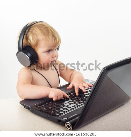 Cute little girl is sitting at table with her black laptop, isolated over white