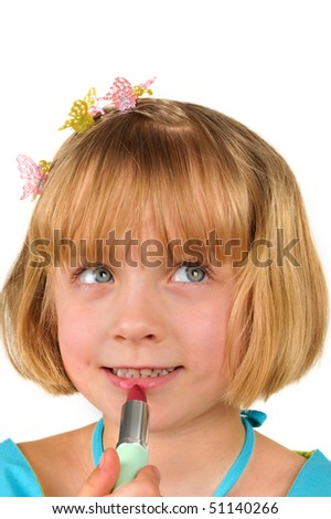 Cute little girl is testing a lipstick - stock photo