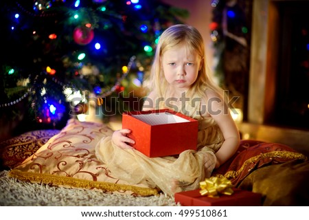 Cute little girl is unhappy with her Christmas gift by a fireplace in a cozy dark living room on Xmas eve