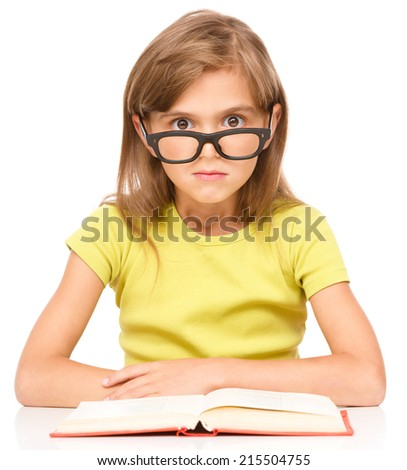 Cute little girl is wearing glasses while reading book, isolated over white - stock photo