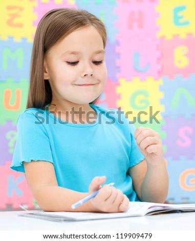 Cute little girl is writing using a pen in preschool - stock photo