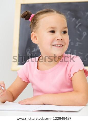 Cute little girl is writing using a pen in school - stock photo
