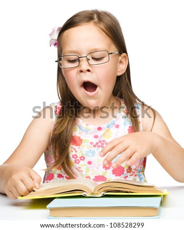 Cute little girl is yawning while reading book and wearing glasses, isolated over white - stock photo