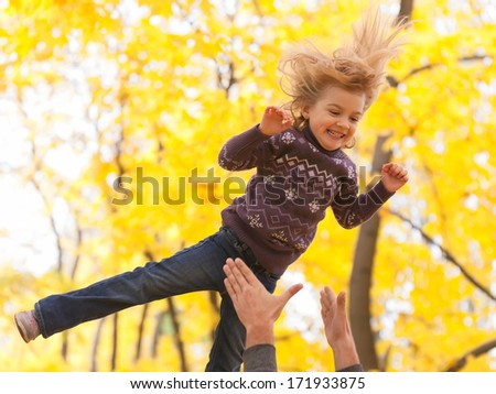 Cute little girl jumping in the autumn forest  - stock photo