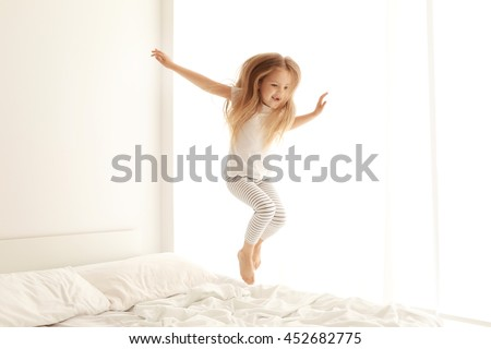 Cute little girl jumping on white bed - stock photo