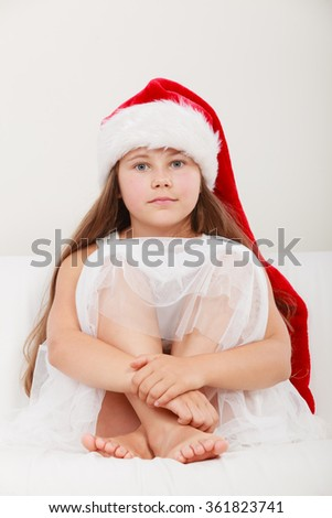 Cute little girl kid in red santa claus hat and white dress sitting on sofa couch. Chrtistmas holiday season.
