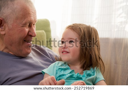 Cute little girl laughing with her grandfather  - stock photo