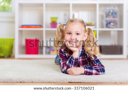 Cute little girl lay on carpet at home - stock photo