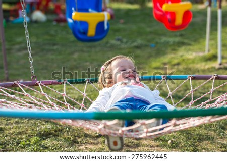 cute little girl laying in a park nest basket swing  - stock photo