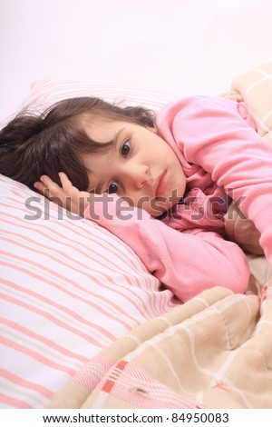 Cute little girl laying in bed and can't fall asleep - stock photo