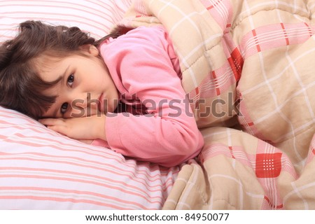 Cute little girl laying in bed and can't fall asleep or is just waking up - stock photo