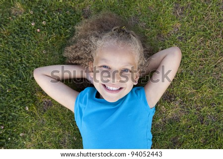Cute little girl laying in the grass - stock photo