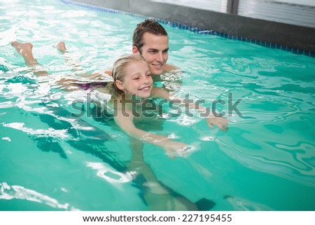 Cute little girl learning to swim with coach at the leisure center - stock photo