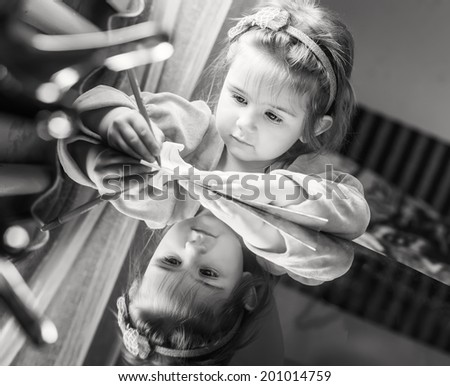 cute little girl learns to write with a pen at home (black and white) - stock photo
