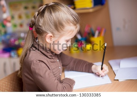 Cute little girl, left-handed, writing her homework at the table