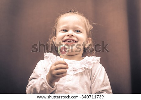 Cute little girl licking lollipop.  - stock photo