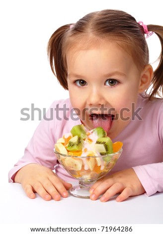 Cute little girl licks fruit salad, isolated over white - stock photo