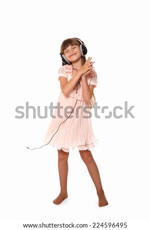 cute little girl listening to music in headphones and dancing. isolated on white background - stock photo