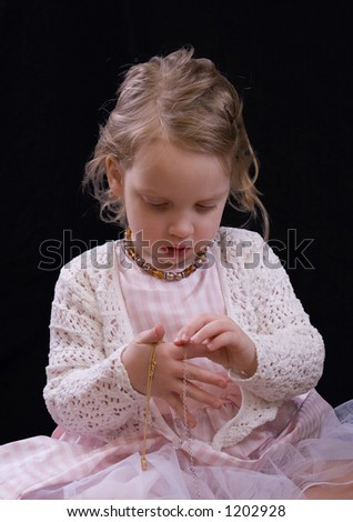 Cute little girl looking at jewelry