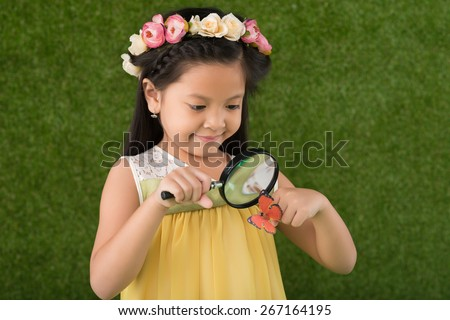 Cute little girl looking at the butterfly through magnifying glass - stock photo