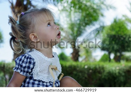 Cute little girl looking at the sky in summer day.