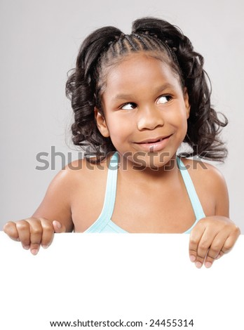 Cute little girl looking away while holding up space for text - stock photo