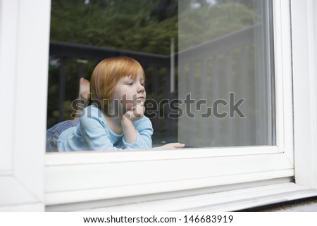 Cute little girl looking out through glass window at home