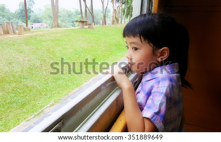 Cute little girl looking out window of a train, blurred