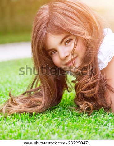 Cute little girl lying down on fresh green grass field, having fun outdoors, relaxing on backyard, happy and carefree childhood - stock photo