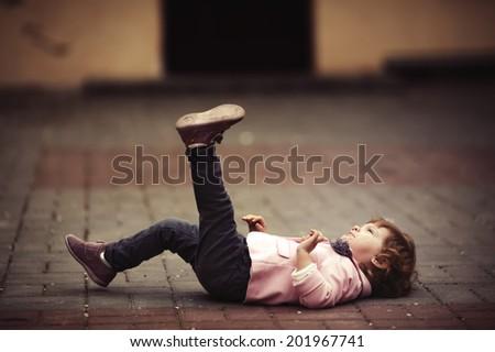 cute little girl lying on asphalt portrait - stock photo