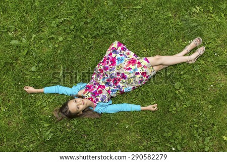 Cute little girl lying on green grass (top view) - stock photo