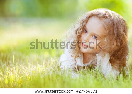 Cute little girl lying on the grass