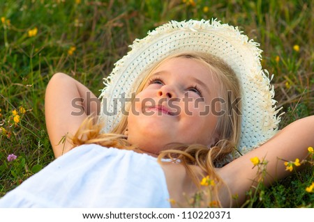 Cute little girl lying on the meadow and daydreaming on beautiful summer day. - stock photo