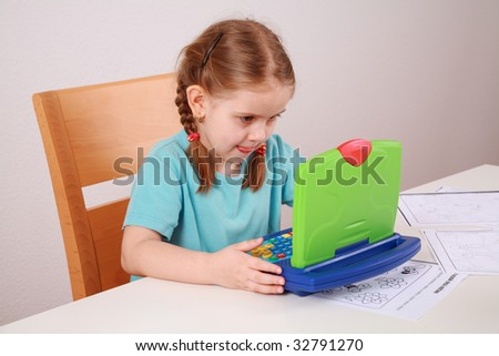 Cute little girl making homework with her computer
