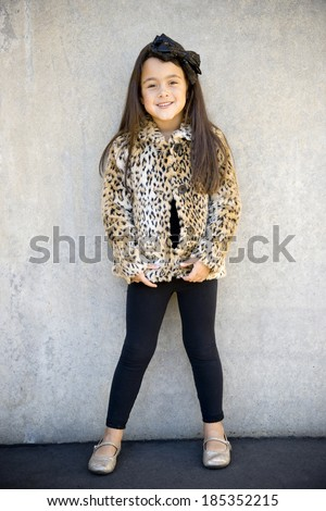 Cute little girl modeling a leopard patterned fur coat, outside, happy expression - stock photo