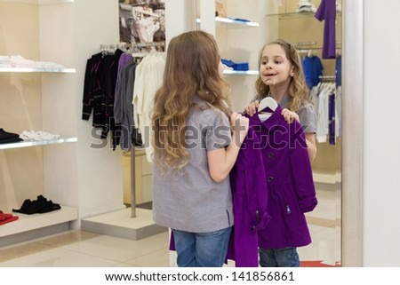 Cute little girl near a mirror try on clothes in a store childrens clothes